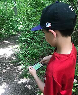 Boy with phone map in woods